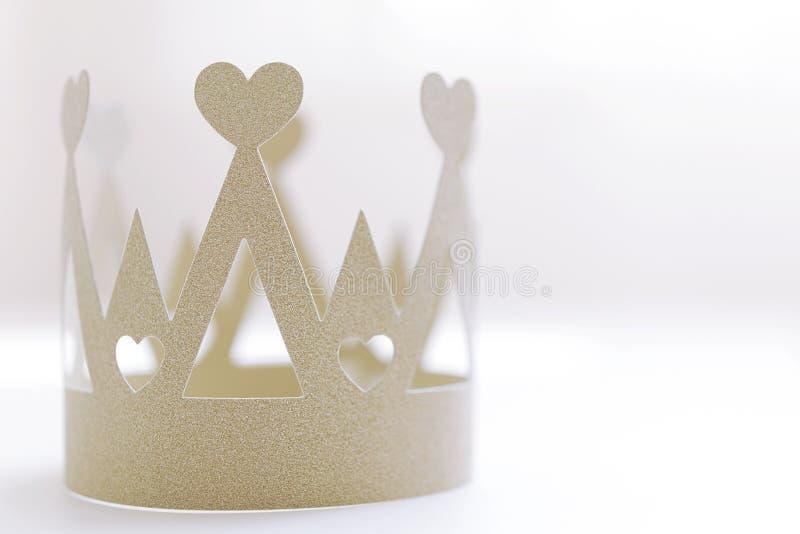 Corona de papel de oro en el fondo blanco fotografía de archivo