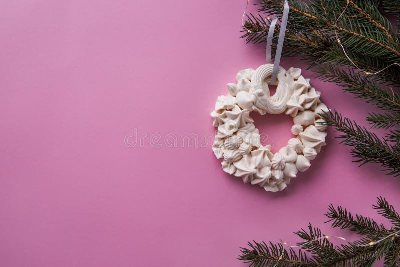 Corona della meringa di Natale sul ramo dell'abete sui precedenti rosa di colore Disposizione piana fotografie stock libere da diritti