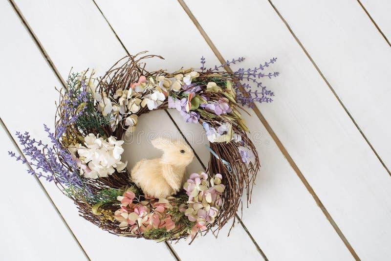 Corona di Pasqua con coniglio Pavimento di legno Fondo pasqua fotografie stock libere da diritti