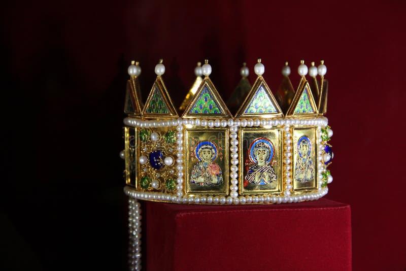 Corona dorata con le icone su un fondo rosso fotografie stock libere da diritti
