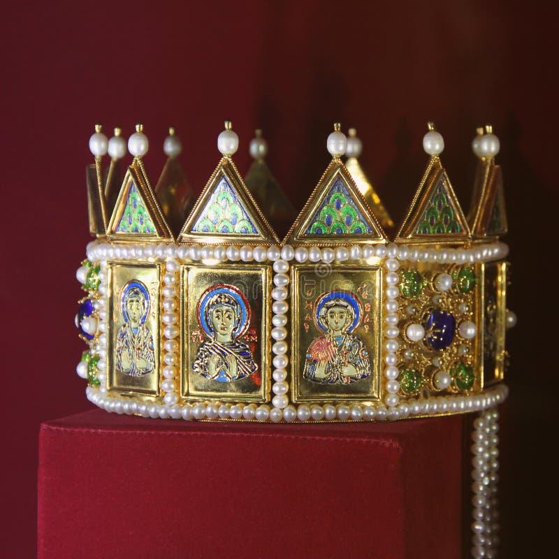 Corona dorata con le icone su un fondo rosso immagine stock libera da diritti