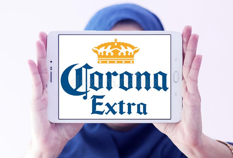 Corona extra beer logo. Logo of Corona extra beer on samsung tablet holded by arab muslim woman. Corona Extra is a pale lager produced by Cervecería Modelo in royalty free stock images