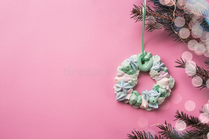 Corona multicolore della meringa di Natale sul ramo dell'abete sui precedenti rosa di colore Disposizione piana immagine stock libera da diritti