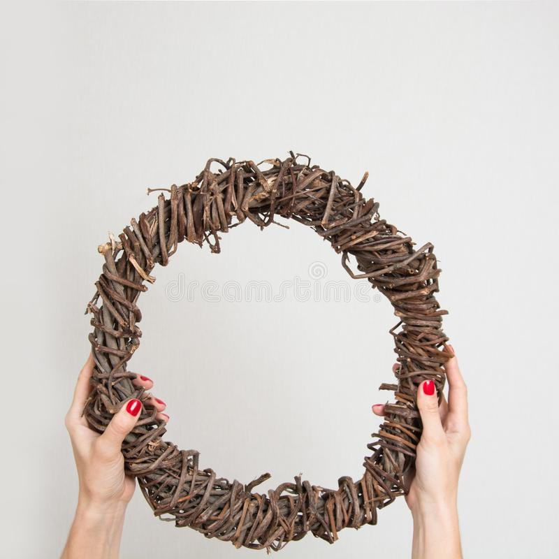 Corona naturale fresca di Natale dalle mani femminili della vite su fondo bianco Preparazione per una corona di Natale immagine stock