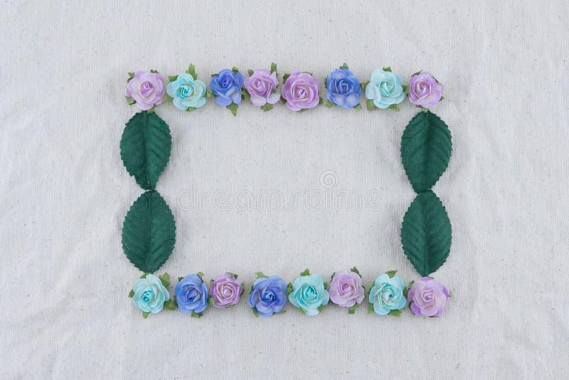 Corona quadrata fatta dai fiori di carta e dalle foglie verdi della rosa blu di tono fotografie stock