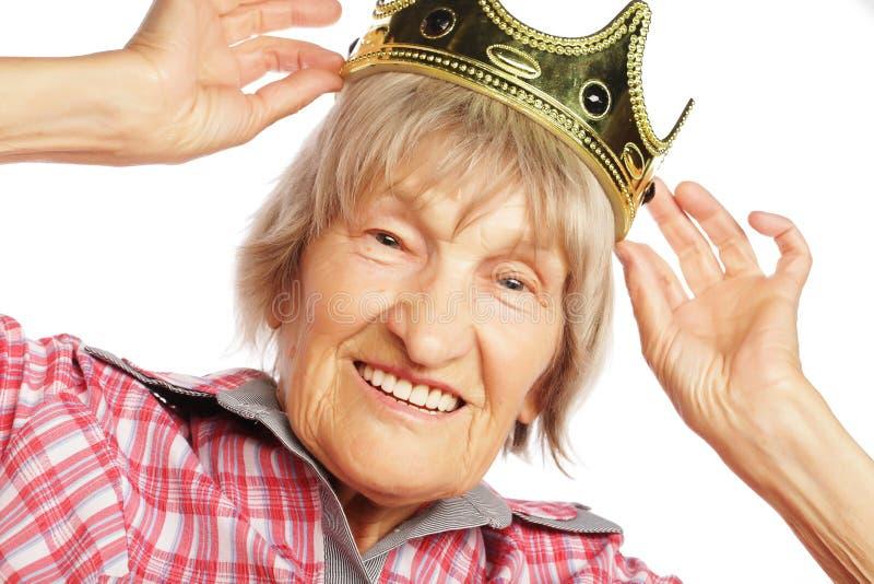 Corona que lleva de la mujer mayor que hace la acción enrrollada foto de archivo