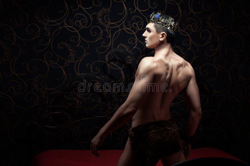 Corona que lleva del hombre hermoso que se coloca en una cama fotos de archivo libres de regalías