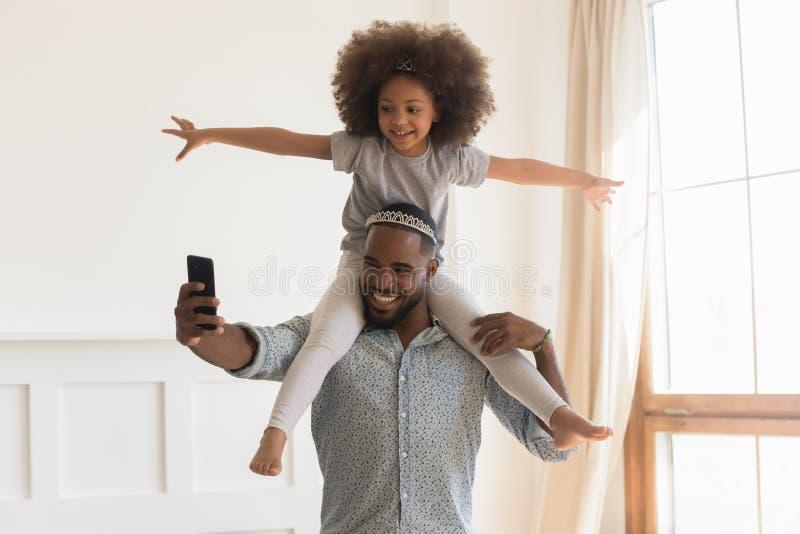 Corona que lleva del papá africano feliz que lleva a cuestas a la pequeña hija que toma el selfie imagen de archivo