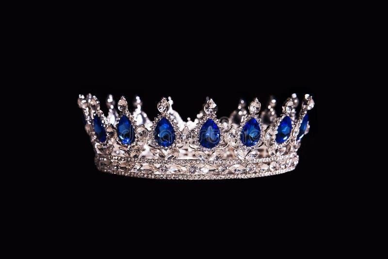 Corona real con el zafiro aislado en fondo negro foto de archivo