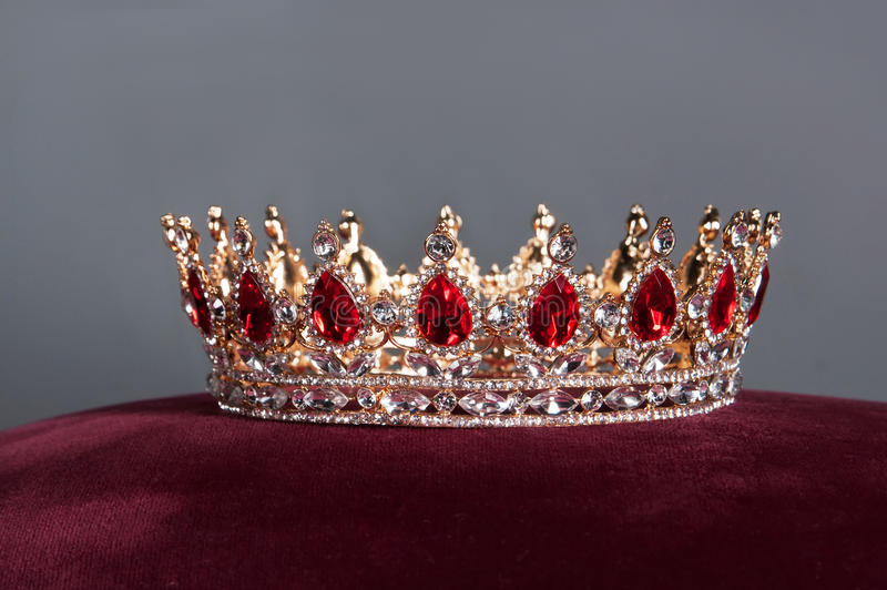 Corona reale con le gemme rosse Rubino, granato Simbolo di potere e di autorità fotografia stock
