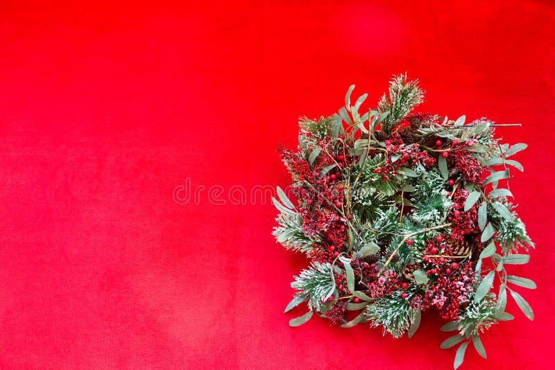 Corona rossa e verde di festa di Natale su fondo rosso fotografie stock libere da diritti