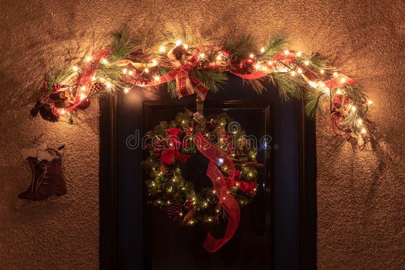 Corona tradizionale di Natale appesa sulla porta con altre decorazioni di festa fotografia stock