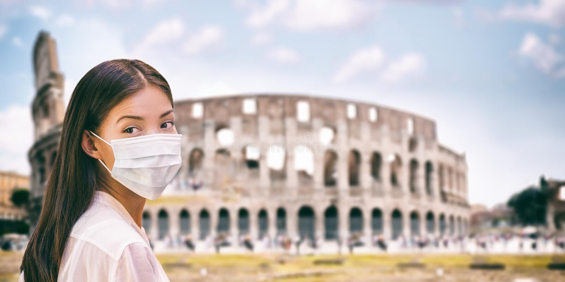 Corona virus Italy travel tourist chinese woman wearing surgical mask protection for coronavirus visiting colosseum. Landmark in Roma, Italy. Travel ban stock photo