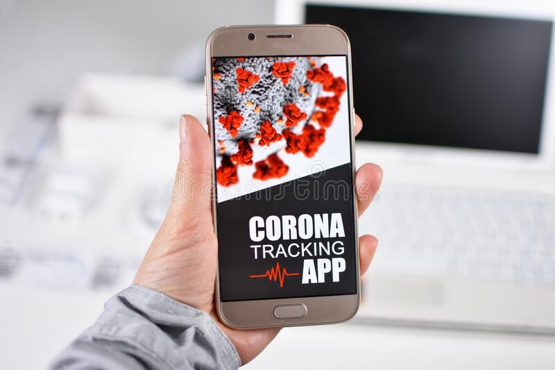 Corona Virus Tracking App concept with hand holding cell phone with application design on screen. In front of blurry office background royalty free stock photo