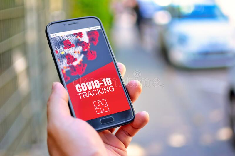 Corona Virus Tracking App concept with hand holding cell phone with application design on screen in front of blurry street. Background stock photo