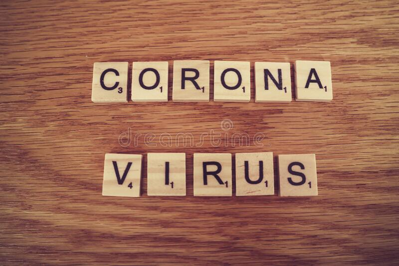 Corona virus. The words corona and virus formed with scrabble tiles letters on a wooden surface royalty free stock photography