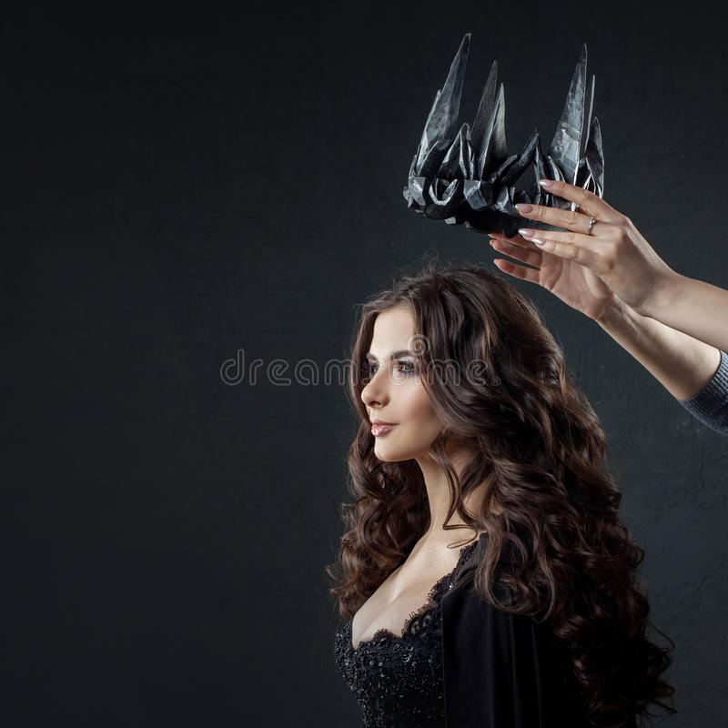 Coronation of the Gothic Queen. Image on Halloween. Hands put a crown on the head of a luxurious woman royalty free stock photo