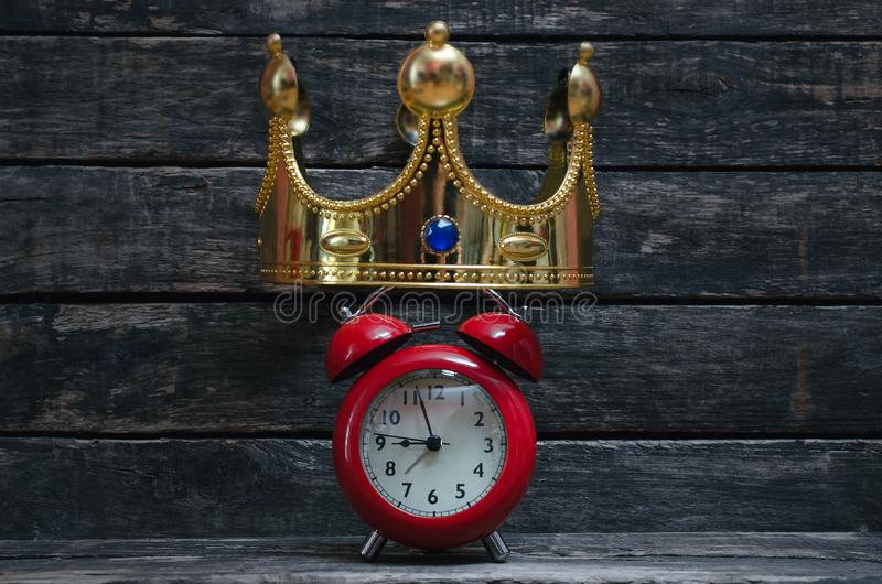 Coronation time. Time to be a leader concept. Coronation or award ceremony time. Red alarm clock under a golden king crown stock images