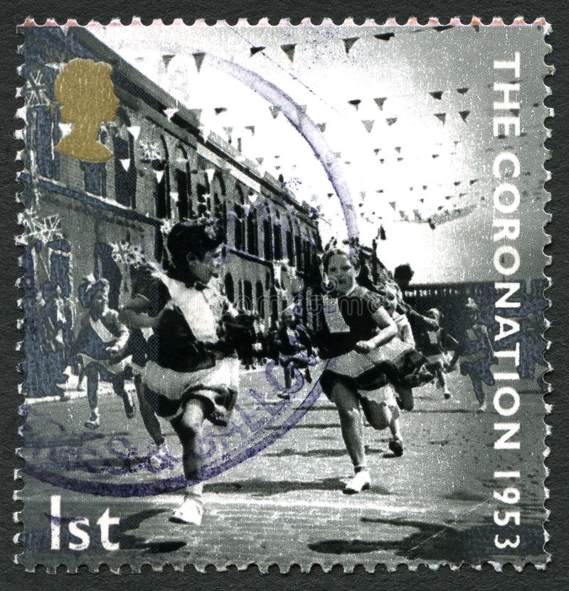 The Coronation UK Postage Stamp. GREAT BRITAIN - CIRCA 2003: A used postage stamp from the UK, depicting a scene from the day of the Coronation of Queen stock photography