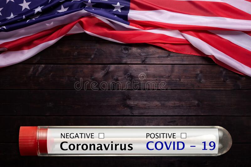 Coronavirus blood test tube and American Flag Laying on a Wooden Background stock images