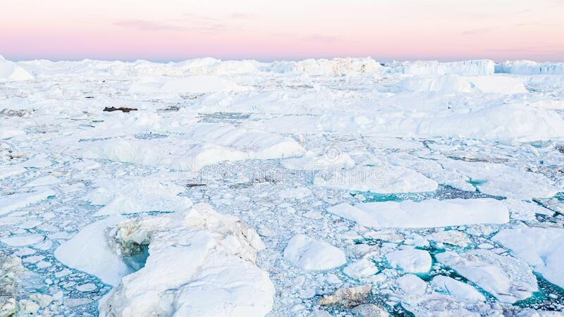 Coronavirus and covid-19 crisis causing less greenhouse gas emissions affecting global warming and climate change. Icebergs in Ilulissat icefjord. Affected by royalty free stock photography