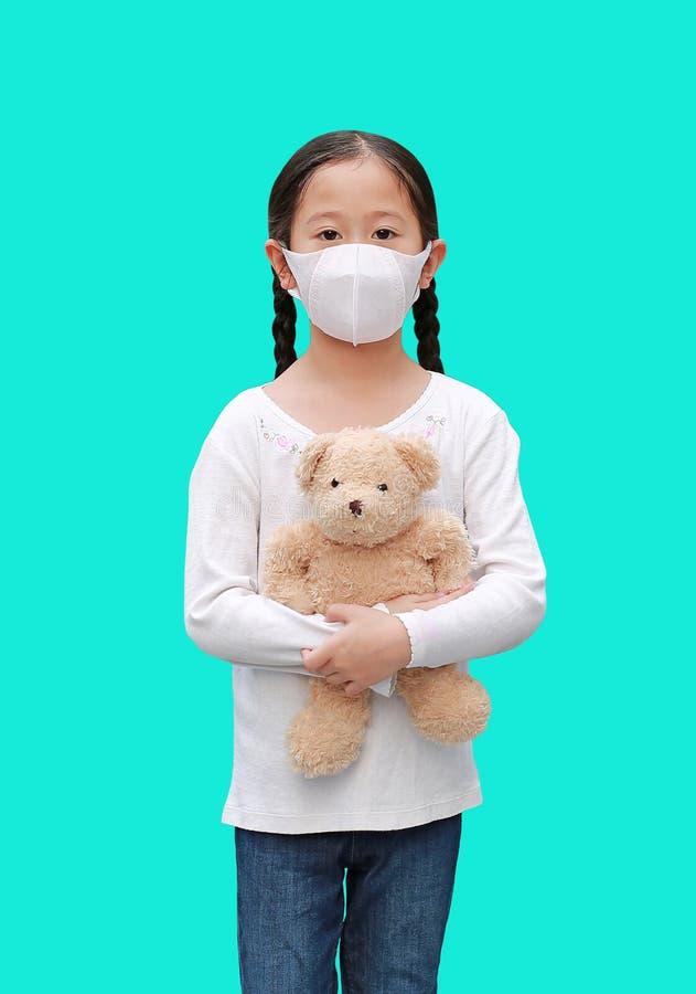 Coronavirus covid-19 e conceito de proteção contra a poluição Garota asiática, boneca de ursinho de pelúcia, com máscara contra imagem de stock