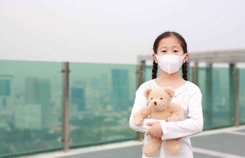 Coronavirus covid-19 e conceito de proteção contra a poluição Menina asiática abraçando a boneca do ursinho de pelúcia com máscar foto de stock royalty free