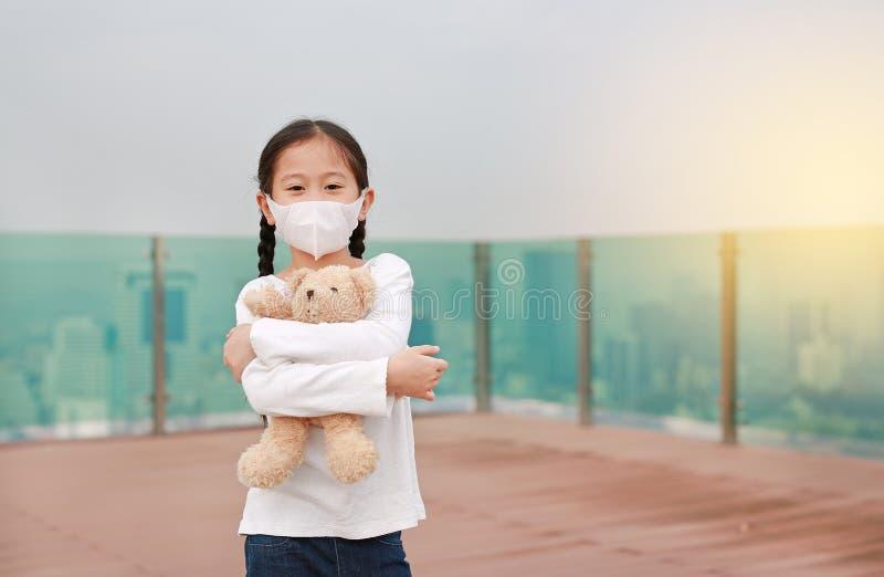 Coronavirus covid-19 e conceito de proteção contra a poluição Menina asiática abraçando a boneca do ursinho de pelúcia com máscar fotografia de stock royalty free