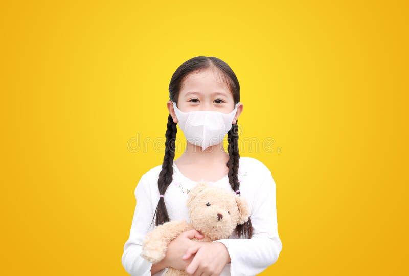 Coronavirus covid-19 e conceito de proteção contra a poluição Menina asiática abraçando a boneca do ursinho de pelúcia com máscar imagem de stock