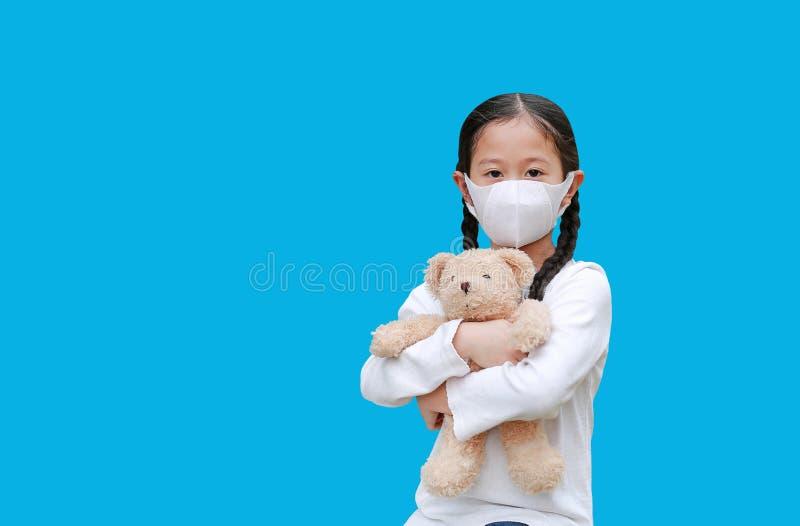 Coronavirus covid-19 e concetto di protezione dall'inquinamento Ragazza asiatica che abbraccia orsacchiotto con una maschera per  fotografie stock