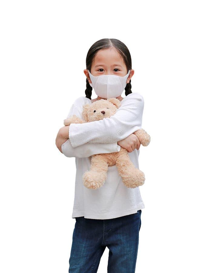 Coronavirus covid-19 i koncepcja ochrony przed zanieczyszczeniami Azjatycka dziewczynka przytulająca lalkę z misiami z maską do obraz royalty free