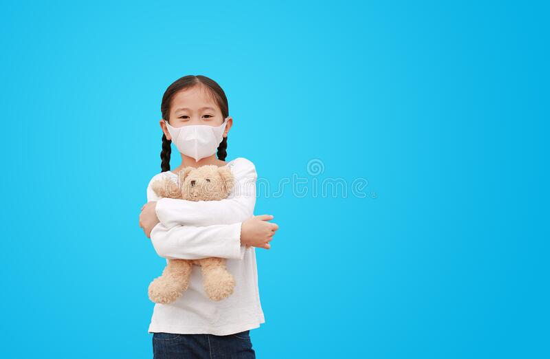 Coronavirus covid-19 i koncepcja ochrony przed zanieczyszczeniami Azjatycka mała dziewczynka przytulająca lalkę z misiami z maską zdjęcie stock
