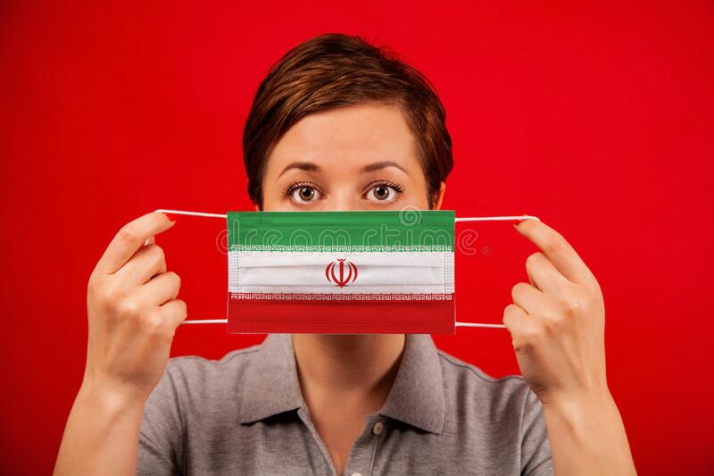 Coronavirus COVID-19 in Iran. Woman in medical protective mask with the image of the flag of Iran. The concept of preventing the spread of the epidemic and royalty free stock photos