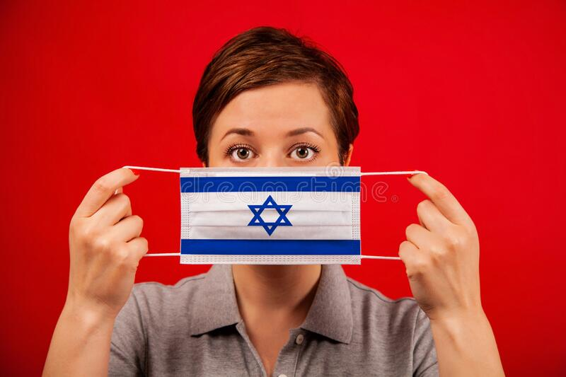 Coronavirus COVID-19 in Israel. Woman in medical protective mask with the image of the flag of Israel. The concept of preventing the spread of the epidemic and stock images
