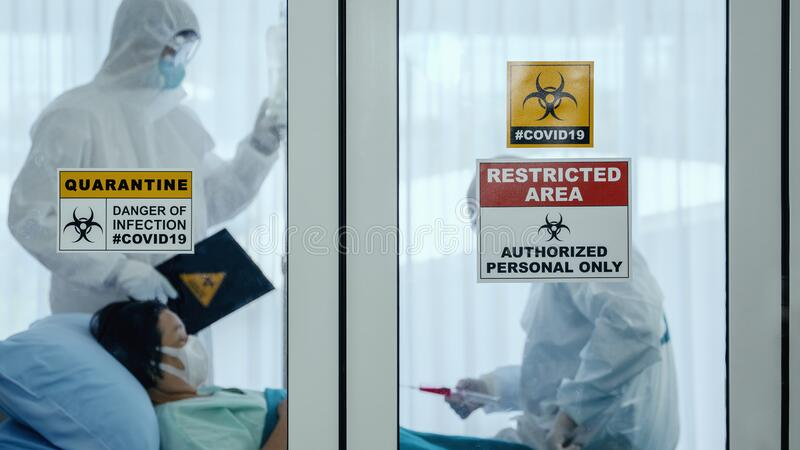 Coronavirus covid-19 quarantine and breakout alert sign on window of quarantine room at hospital with disease control experts try. To make disease treatment to stock images
