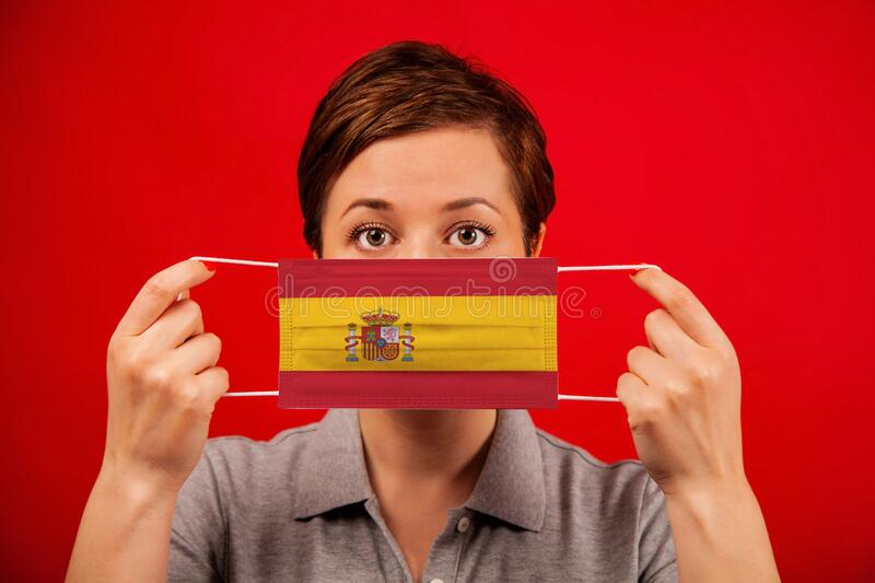 Coronavirus COVID-19 in Spain. Woman in medical protective mask with the image of the flag of Spain. The concept of preventing the spread of the epidemic and royalty free stock photos
