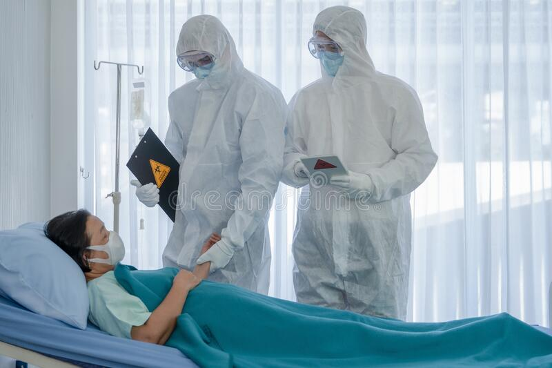 Coronavirus covid 19 treatment background of coronavirus covid 19 patient on bed with doctors in PPE coverall suit in hospital. Negative pressure quarantine stock image
