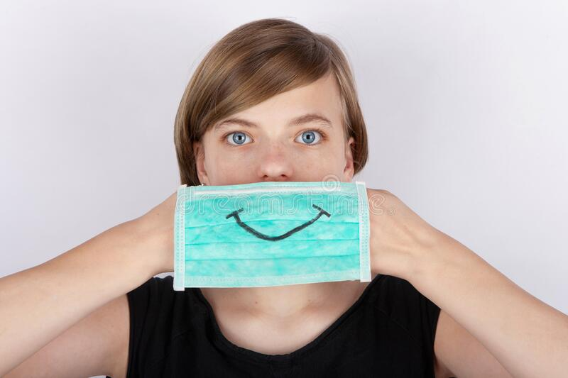 Coronavirus and face mask - Girl holding a face mask with a smile drawing in front of her face royalty free stock photo