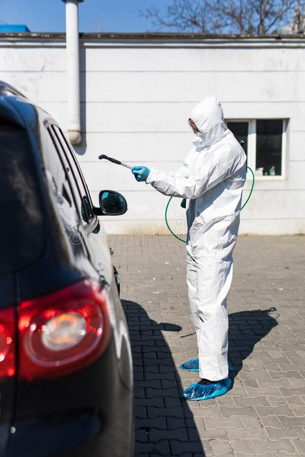 Coronavirus Pandemic. Disinfector in a protective suit and mask sprays disinfectants of car outdoors stock images