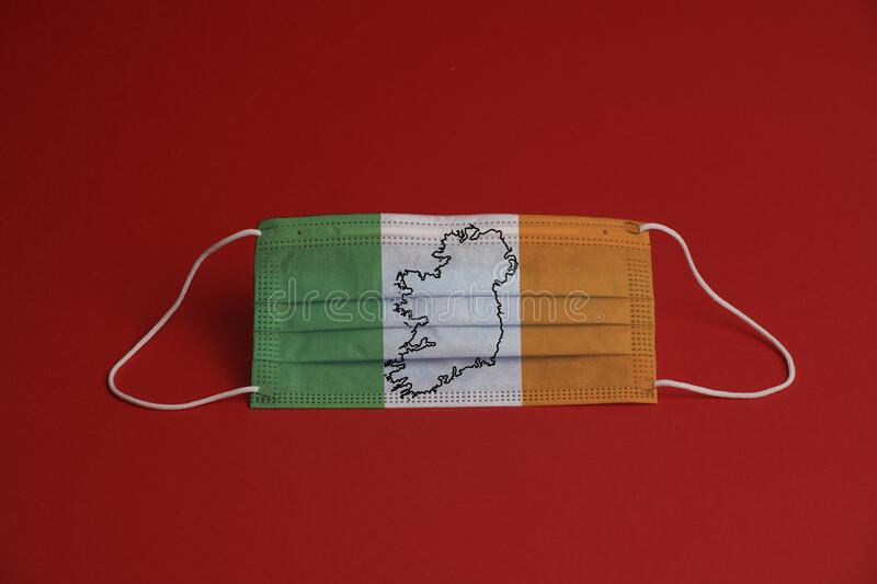 Coronavirus protective mask. Medical mask Ireland flag and map. Red background. Face mask protection against pollution, virus, flu. Healthcare and surgery stock images