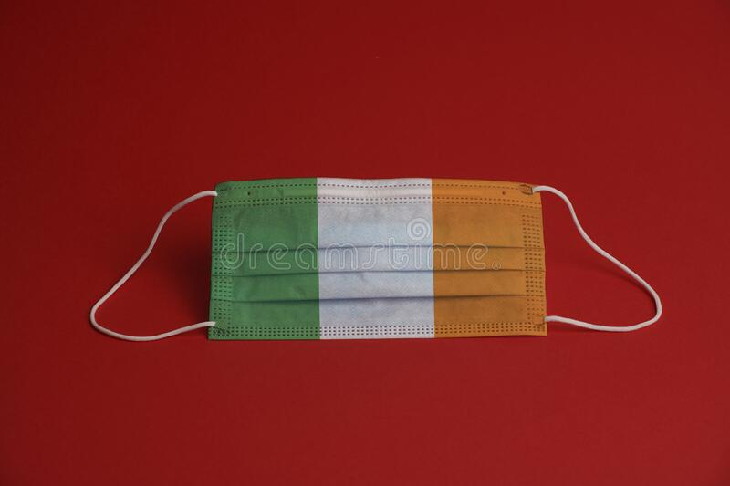 Coronavirus protective mask. Medical mask combined with the Ireland flag. Red background. Face mask protection against pollution,. Virus, flu. Healthcare and royalty free stock photography