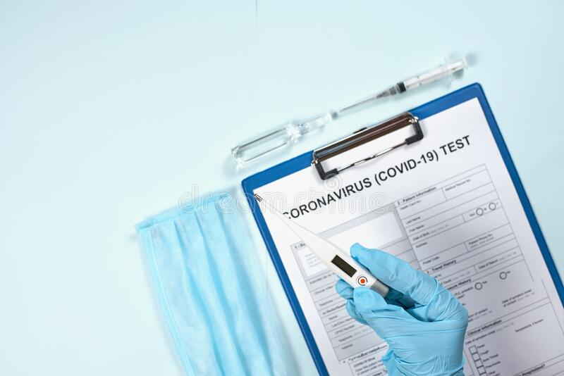 Test form. Doctor holding thermometer over the test form. Getting the COVID-19 test. Testing for 2019-ncov. Medical test form for new corona virus with medical stock image