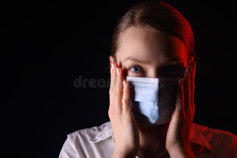 Coronavirus, una chica enmascarada en un fondo negro Título sobre el brote del virus de la corona en China, enfermedad Epidemia fotografía de archivo