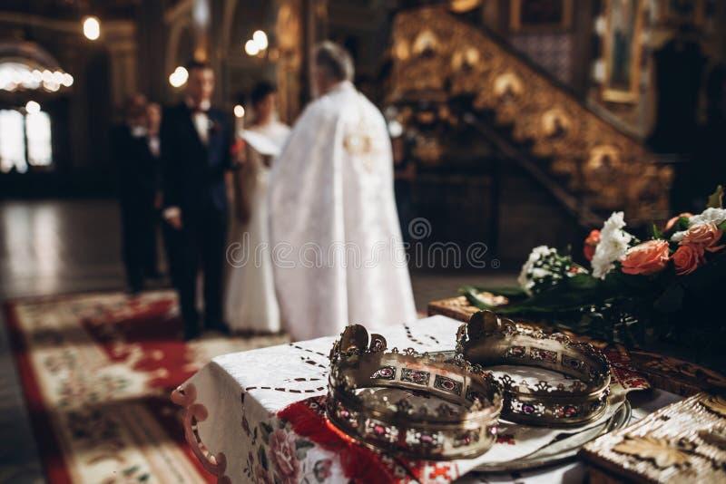 Corone dorate sull'altare e sul sacerdote che mettono sulla fede nuziale dorata fotografie stock