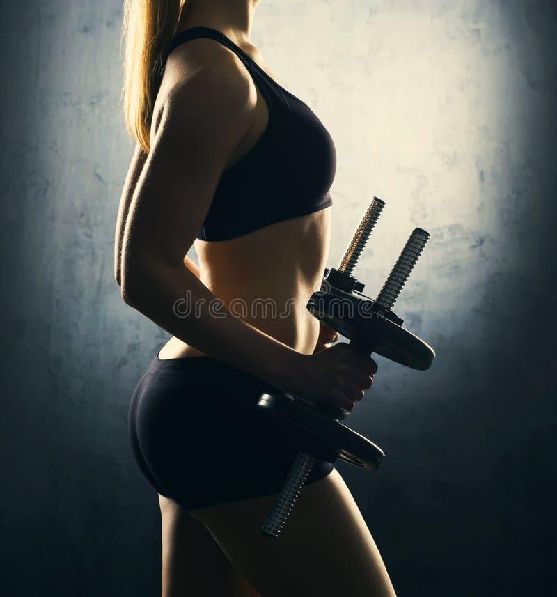 Corpo apto da mulher bonita, saudável e desportiva com pesos Mulher magro que levanta no sportswear fotografia de stock royalty free