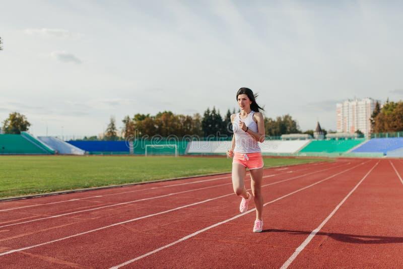 Corpo completo da pista de atletismo da menina no est?dio Opinião dianteira real a jovem mulher no short cor-de-rosa e a camiseta fotografia de stock royalty free