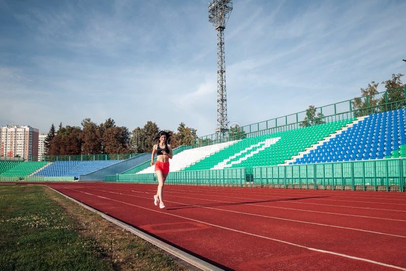 Corpo completo da pista de atletismo da menina no est?dio Opinião dianteira real a jovem mulher no short cor-de-rosa e a camiseta fotos de stock