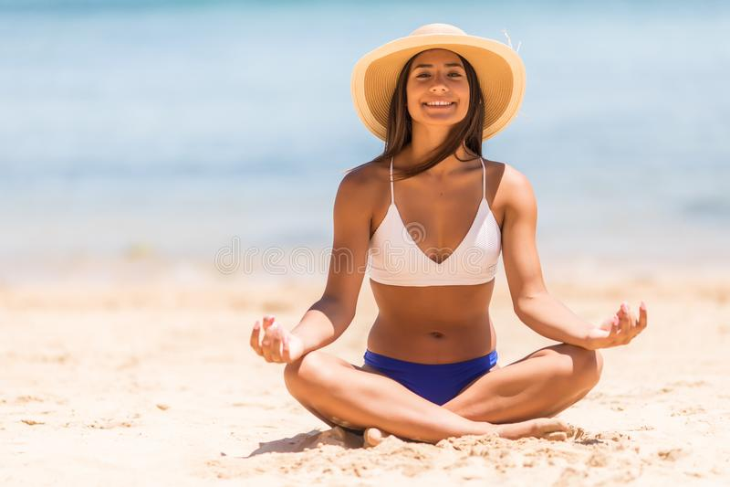 Corpo completo de um biquini vestindo da menina que faz exercícios da ioga na praia no mar imagens de stock