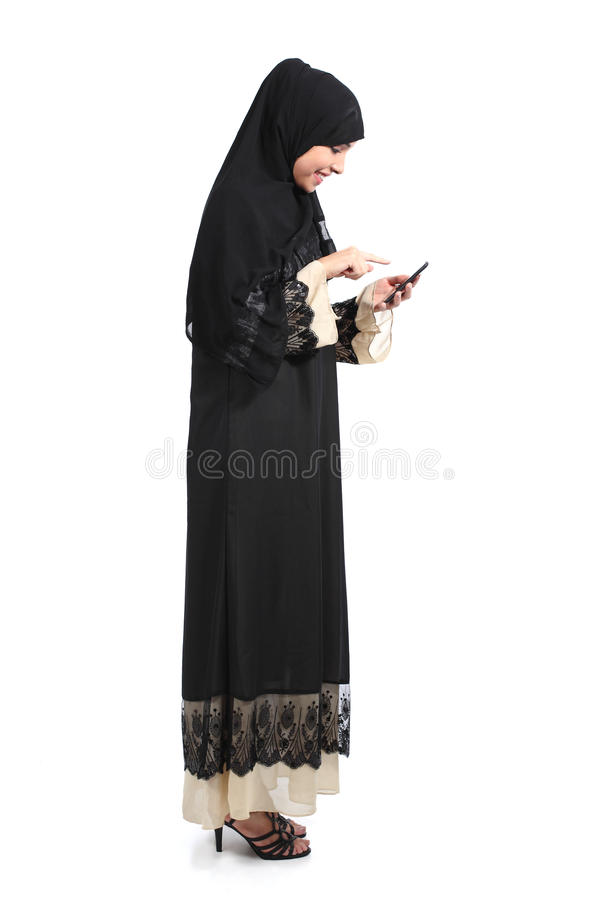 Corpo completo de uma mulher árabe do saudita que consulta um telefone esperto fotos de stock