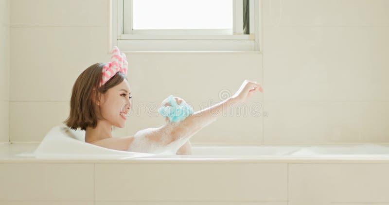 Corpo da lavagem da mulher na banheira imagens de stock royalty free
